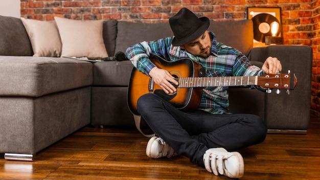 Full shot mann auf dem boden spielt gitarre Kostenlose Fotos