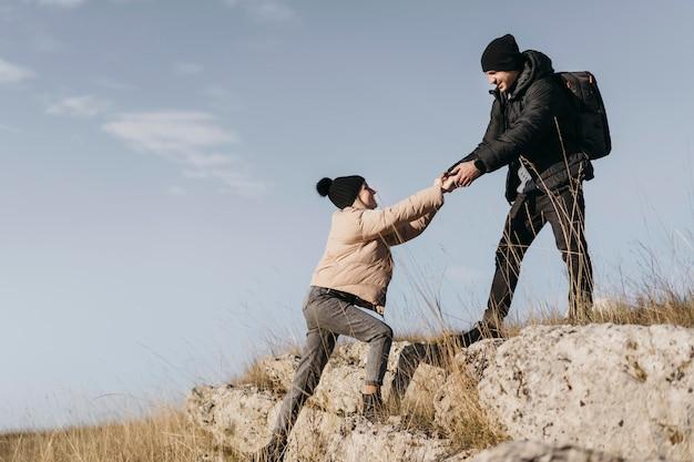 Full shot mann hilft frau klettern Kostenlose Fotos