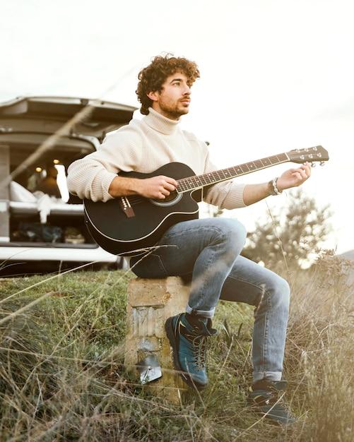 Full shot mann spielt gitarre Kostenlose Fotos