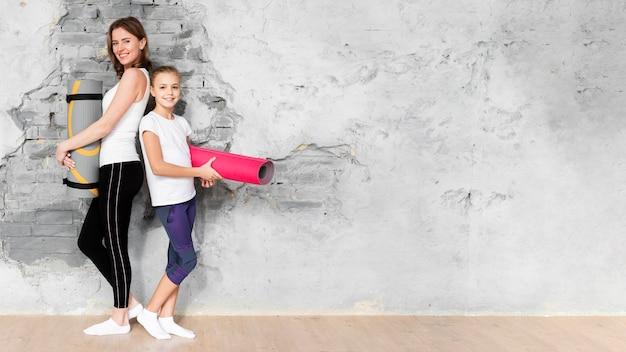 Full shot mutter und kind halten yogamatten mit kopierraum Premium Fotos
