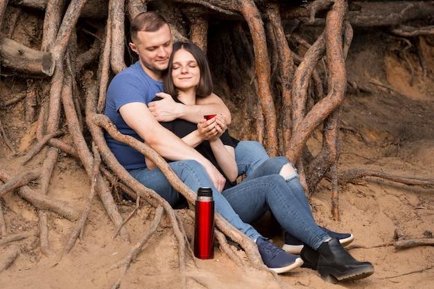 Full shot paar sitzt zusammen Premium Fotos