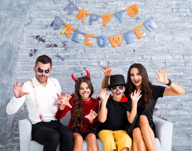 Furchtsame familie, die zusammen für halloween aufwirft Kostenlose Fotos