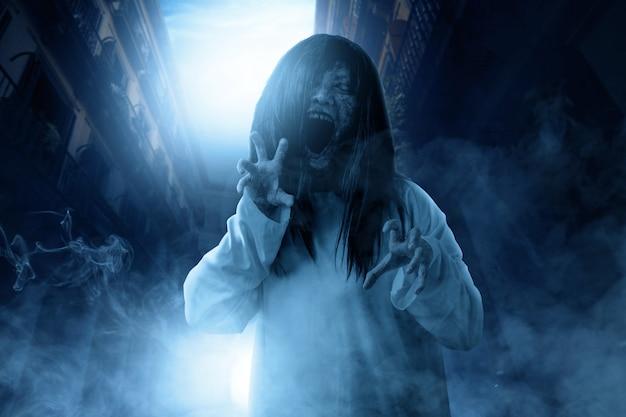 Furchtsame geistfrau mit blut und verärgertem gesicht mit den greiferhänden frequentierte das verlassene gebäude Premium Fotos