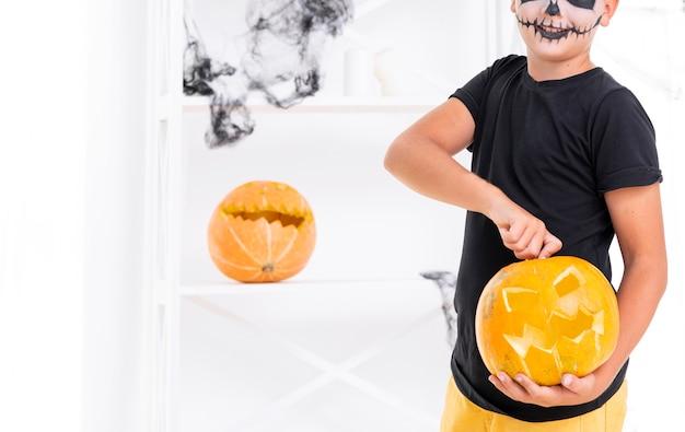 Furchtsamer junge, der geschnitzten kürbis für halloween hält Kostenlose Fotos