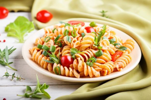 Fusilli-teigwaren mit tomatensaucekirschtomatenkopfsalat und -kräutern auf einem weißen hölzernen hintergrund Premium Fotos