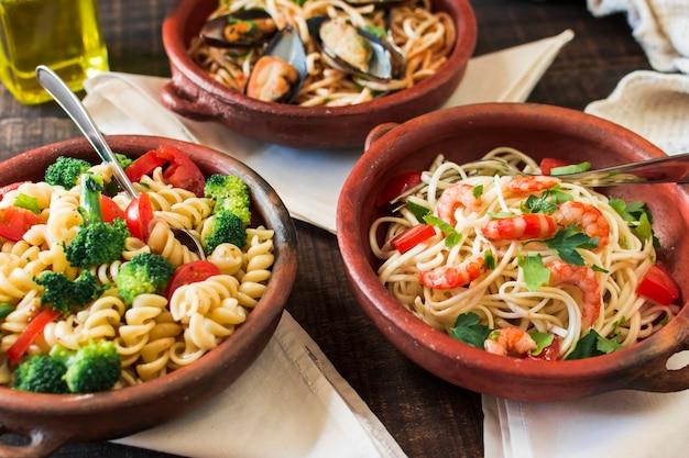 Fusilli und spaghettiteigwaren in der töpferware auf tabelle mit servietten Kostenlose Fotos