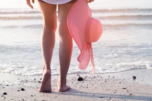 Fuß der frau gehend auf den strand mit dem halten des rosa hutes Premium Fotos