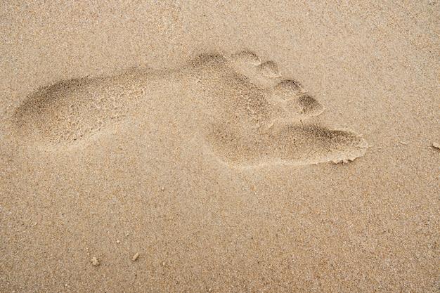 Fußabdruck auf dem strandsandhintergrund. Premium Fotos