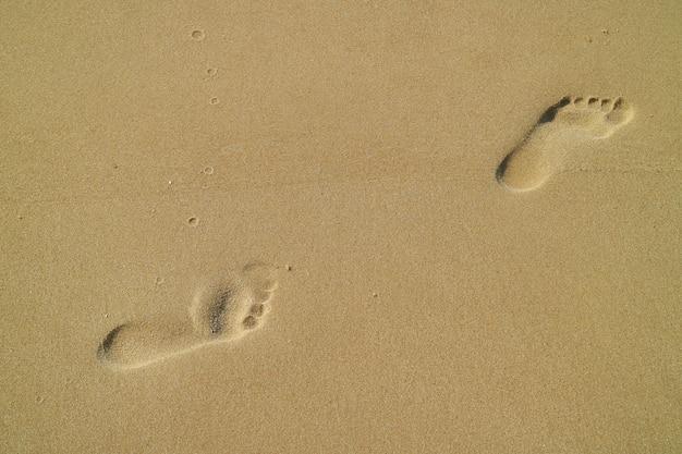 Fußabdrücke einer frau am sandstrand Premium Fotos