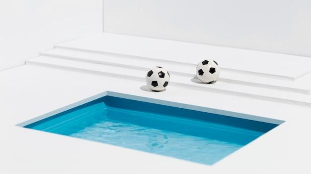 Fußbälle neben dem kleinen schwimmbad Kostenlose Fotos