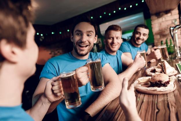 Fußballfans schauen sich das spiel mit bier an und essen. Premium Fotos