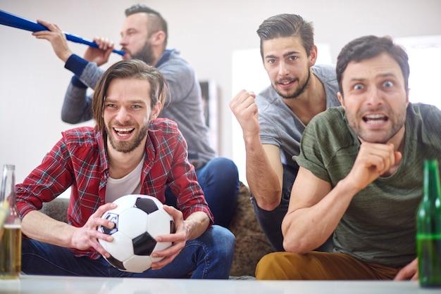 Fußballfans schauen sich das spiel zu hause an Kostenlose Fotos