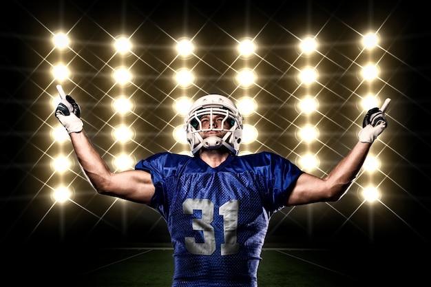 Fußballspieler mit einer blauen uniform, die vor lichtern feiert Kostenlose Fotos