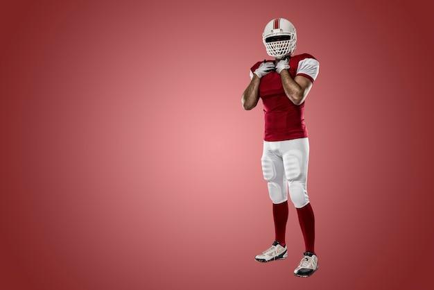 Fußballspieler mit einer roten uniform an einer roten wand Premium Fotos