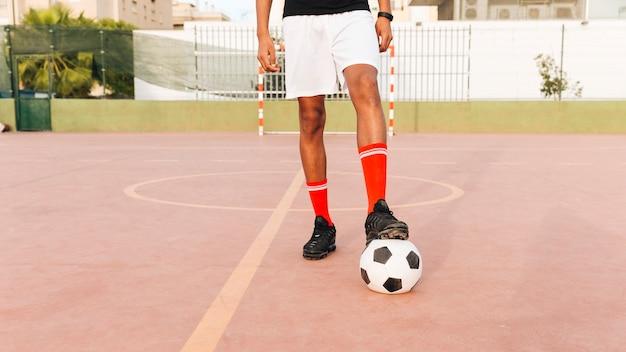 Fußballspielerfüße auf fußball am stadion am sonnigen tag Kostenlose Fotos