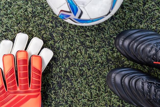 Fußballstollenschuhe mit fußball und handschuh auf künstlicher rasenfläche Premium Fotos