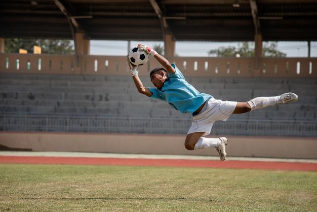 Fußballtorhüter in der aktion auf dem fußballstadion Premium Fotos