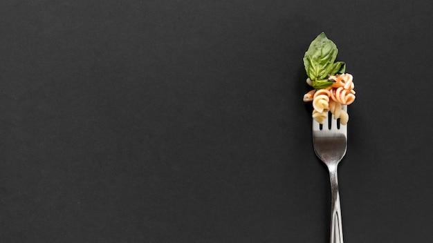 Gabel mit fusilli teigwaren und basilikumblättern über schwarzem hintergrund Premium Fotos