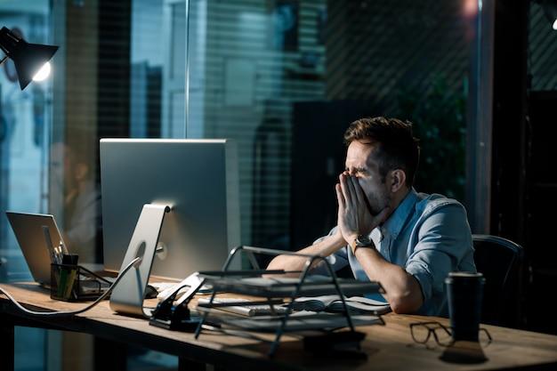 Gähnender müder mann, der stundenlang arbeitet Premium Fotos