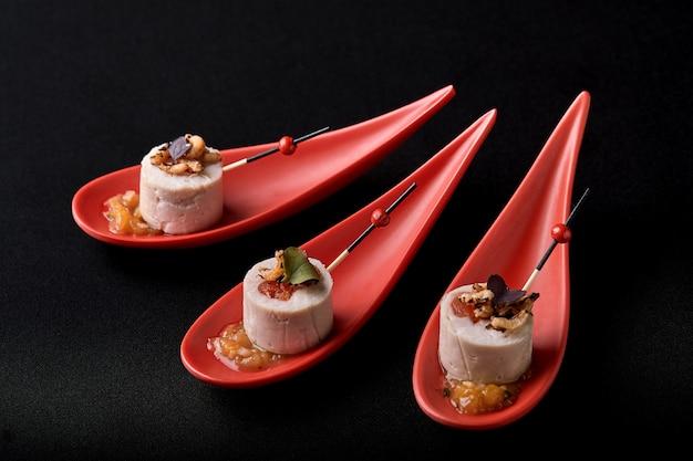 Gänseleberpastete, foie gras, serviert auf schwarzem stein in japanischen roten löffeln. paste mit marmelade und nüssen serviert. fusionslebensmittelkonzept, zurückhaltend, kopienraum. Premium Fotos