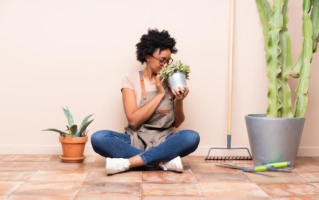 Gärtnerfrau, die auf dem boden sitzt Premium Fotos