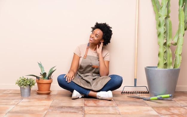 Gärtnerfrau, die auf dem boden unter anlagen sitzt Premium Fotos