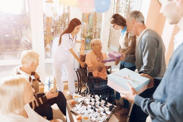 Gäste geben der älteren frauen-geburtstagsfeier geschenke Premium Fotos