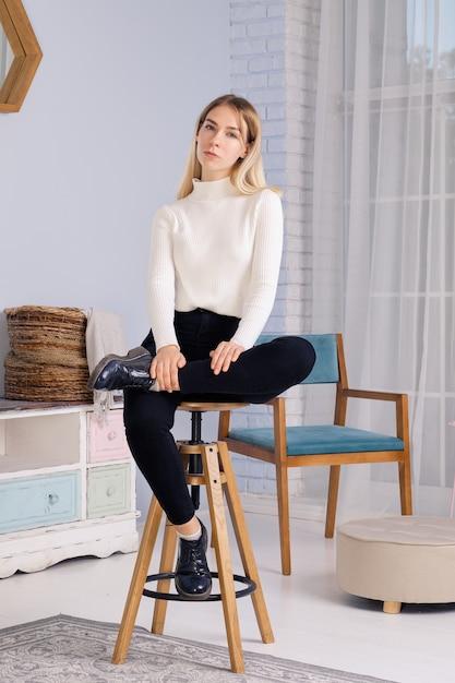 Ganzaufnahme des jungen mädchens sitzend auf stuhl im wohnzimmer Premium Fotos
