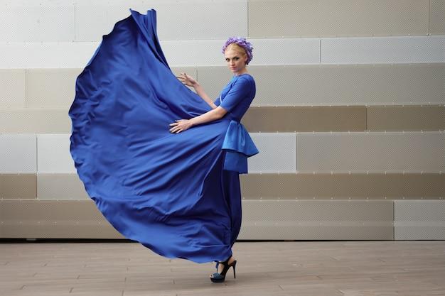 Ganzaufnahme einer modefrau mit ihrem kleiderfliegen in der luft Premium Fotos