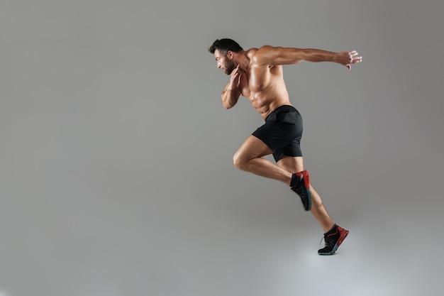 Ganzaufnahme eines hemdlosen männlichen bodybuilders des gesunden sitzes Kostenlose Fotos