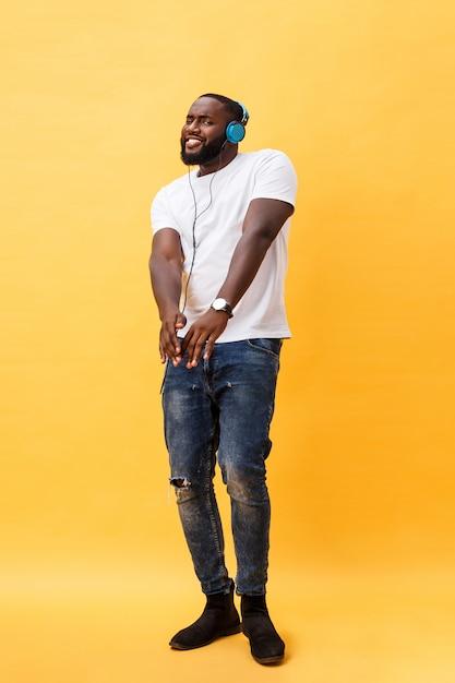 Ganzaufnahme eines jungen afroamerikanischen mannes der kirsche, der musik mit kopfhörern hört Premium Fotos