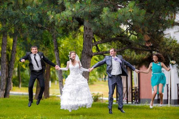 Ganzaufnahme von jungvermähltenpaaren mit den brautjungfern und groomsmen, die in grünen sonnigen park springen Premium Fotos