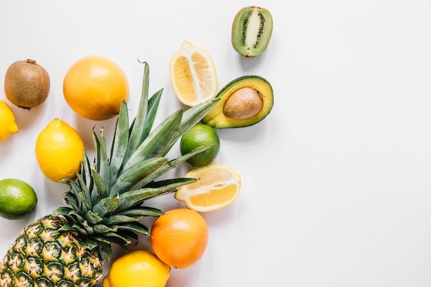 Ganze ananas in der nähe von früchten Kostenlose Fotos