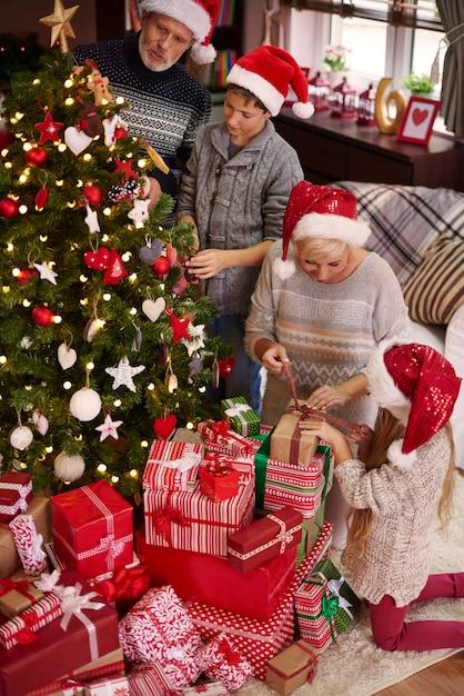 Ganze familie um den weihnachtsbaum Kostenlose Fotos