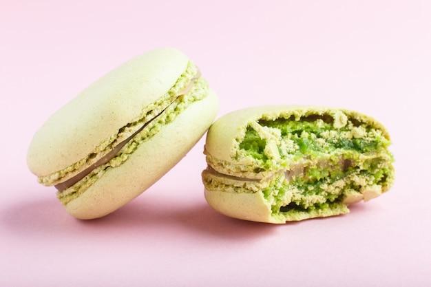 Ganze und gebissene grüne macarons oder makronen backen auf pastellrosahintergrund zusammen Premium Fotos
