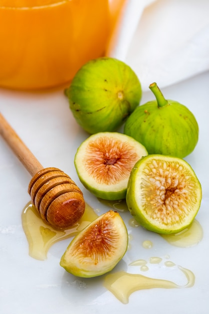 Ganze und geschnittene grüne feigen mit honig. Premium Fotos