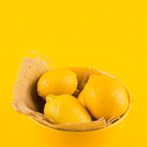 Ganze zitrone in der schüssel gegen gelben hintergrund Kostenlose Fotos