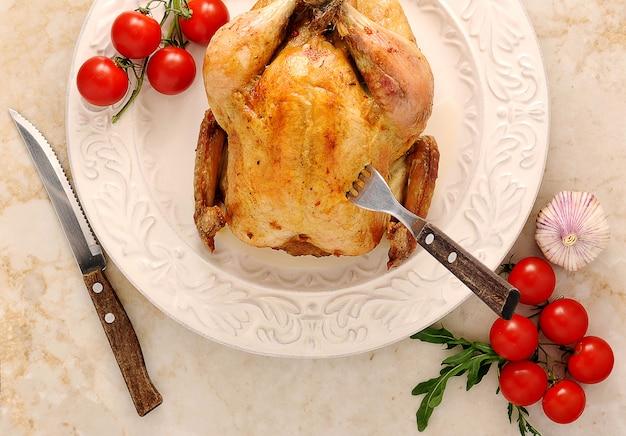 Ganzes gebratenes huhn auf einer platte mit tomaten und basilikum Premium Fotos