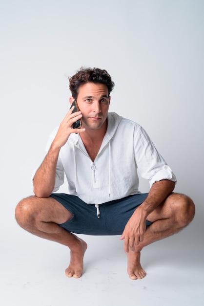 Ganzkörperaufnahme des hübschen hispanischen mannes, der hockt, während er am telefon spricht Premium Fotos