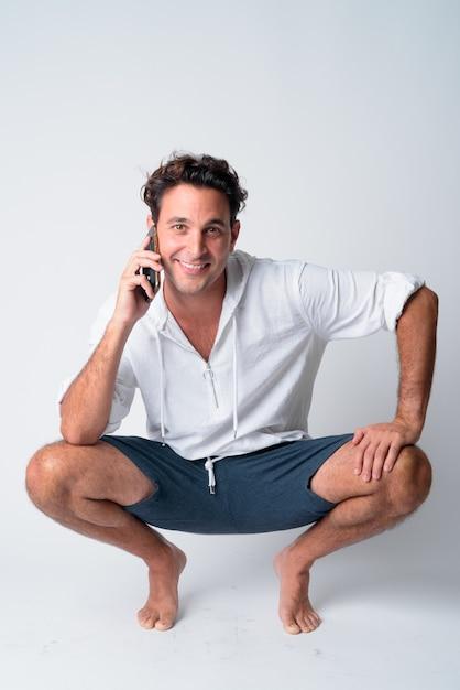 Ganzkörperaufnahme eines glücklichen hispanischen mannes, der sich hockt, während er am telefon spricht Premium Fotos
