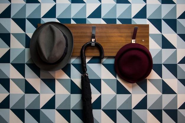 Garderobe mit einigen hüten und einem regenschirm an einer blauen dreieckswand Premium Fotos