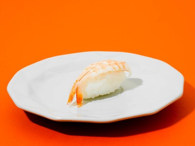 Garnelensushi auf einer weißen platte auf orange hintergrund Premium Fotos