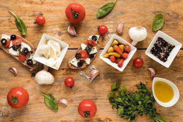 Garnieren sie bruschetta und frischen bestandteil für das kochen auf brauner tabelle Kostenlose Fotos