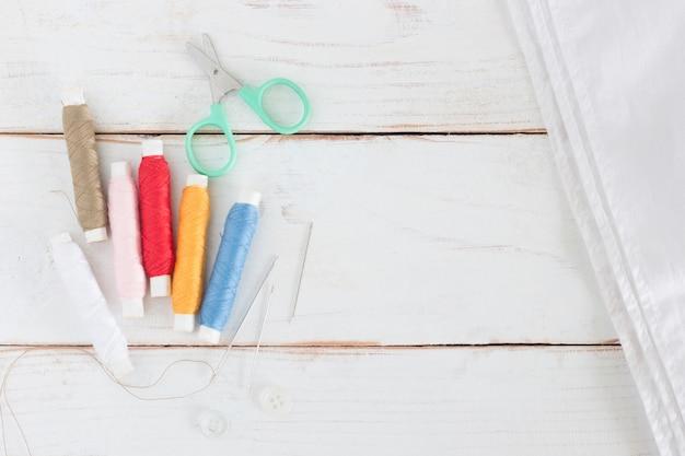 Garnrolle viele färben mit nadel und kleinen scheren auf weißem hölzernem brett Premium Fotos
