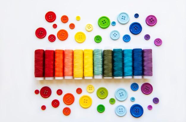 Garnrollen und knöpfe in den farben der regenbogen Premium Fotos
