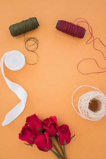 Garnspulen; weißes band; fadenspule und rote rosen auf einem orangefarbenen hintergrund Kostenlose Fotos