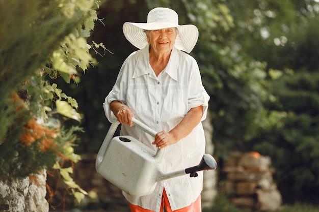 Gartenarbeit im sommer. frau, die blumen mit einer gießkanne wässert. alte frau, die einen hut trägt. Kostenlose Fotos