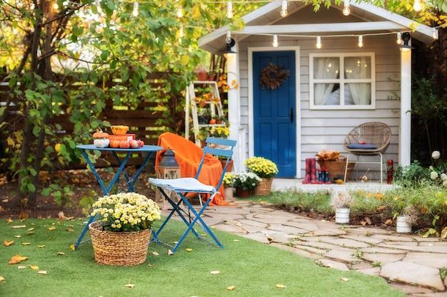 Gartentisch und stühle mit äpfeln und kürbissen auf herbsthof. halloween. gemütliche innenterrasse Premium Fotos
