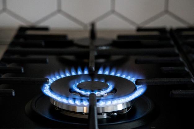 Gasbrenner auf schwarzem modernem küchenofen. küchengaskocher mit brennendem propangas. Premium Fotos
