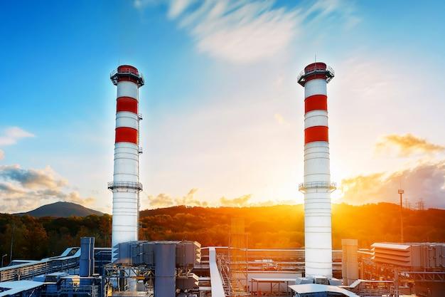 Gaskraftwerk mit zwei langen rohren weißer farbe mit rotem poloskai auf von bergen und von sonnenaufgang. Premium Fotos